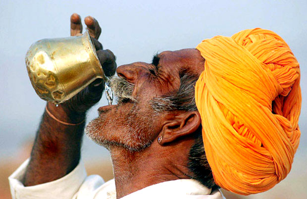 Man drinking water on copper pot